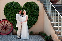 Newlyweds by heart shaped bush (thumbnail)