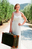 Bride with suitcase on country road, hand on hip