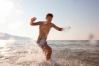 Young man splashing in sea