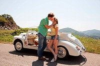Young couple by convertible car kissing (thumbnail)