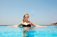 Young woman in infinity pool, looking at camera (thumbnail)