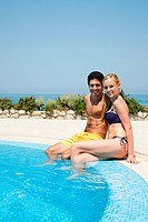 Young couple sitting at poolside