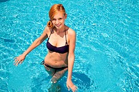 Young woman in swimming pool, high angle