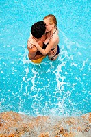 Young couple kissing in swimming pool, high angle