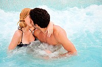 Young couple kissing in hot tub