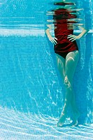Woman standing with hands on hips in swimming pool, underwater view