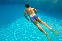 Young man swimming underwater in swimming pool