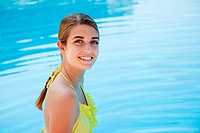 Young woman in yellow bikini by swimming pool, portrait