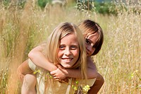Girl giving friend piggy back in field