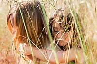 Girl giving friend piggy back in field, close up (thumbnail)