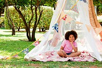 Girl sitting in summer netting tent