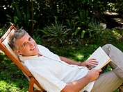 Man sitting on deckchair in garden with book
