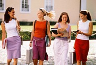 Four young women walking along the street