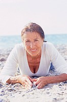 Smiling Senior Woman Lying on Beach