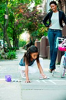 Mother watching daughter draw on sidewalk