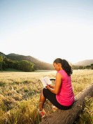 Black woman reading book in remote area