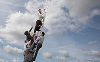 Business people chasing co_worker up ladder into clouds