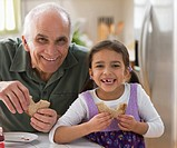 Grandfather and granddaughter eating sandwiches