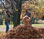 Black family raking autumn leaves