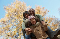Black family hugging in park in autumn