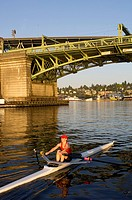 Person rowing sculling boat on river under bridge
