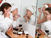 Women applying Make Up in Mirror