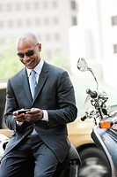 Black businessman sitting on scooter text messaging