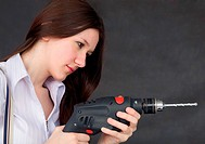 Female student learns to use a drill