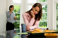 Woman Reading, Man on Cellphone in Kitchen