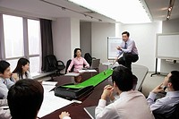 Businessman Using Putting Green During Meeting