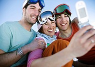 Three Snowboarders Using Camera Phone for Group Photo
