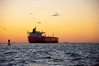 Oil tanker cargo freight ship leaving port at sunset