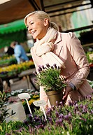 woman buying fresh herbs at weekly market