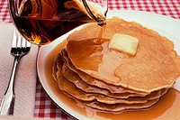 Pouring Maple Syrup on Plate of Pancakes