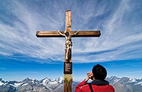 A Chinese tourist prays in front of crucified Christ on top of the Klein Matterhorn, Switzerland, Alps