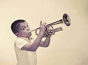 Boy playing trumpet, portrait