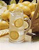 Lemons in basket and jug of lemon juice in front, close_up