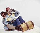 Young couple tobogganing, smiling
