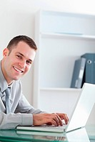 Smiling happy businessman typing on his laptop
