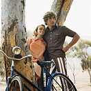 Young couple leaning on tree with bicycle, smiling