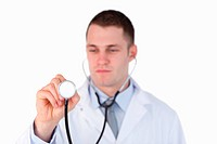 Close up of doctor looking at his stethoscope on white background