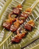 Prawns and meat kebabs on banana leaf, close_up