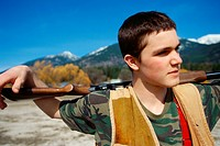 Adolescent Boy Carrying a Rifle on His Shoulders