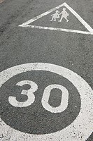 Road sign warning motorists that a school zone and a zone 30 is ahead