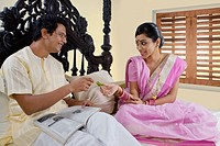 Bengali woman offering paan to her husband