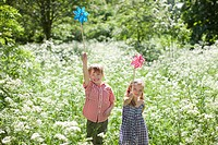 Children playing with pinwheels in field of flowers