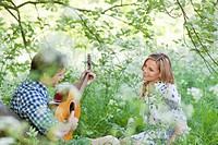 Man playing guitar for girlfriend in field of flowers