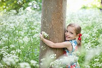 Girl hugging tree in field of flowers