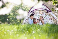 Family sitting in tent in park