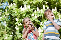 Children licking ice cream outdoors